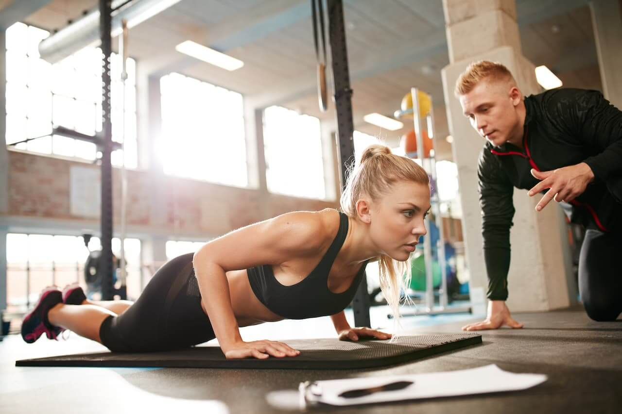Mulher malhando com profissional de educação física